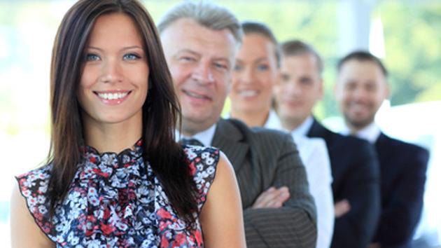 Porträt einer Frau in Bluse, hinter der einige aufgereihte Personen in Anzügen stehen, die lächeln