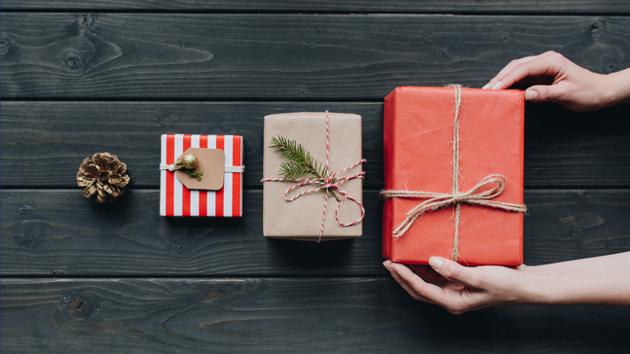 Drei der Größe nach aufgereihte Geschenke liegen auf einem Holzuntergrund und werden von Händen berührt.