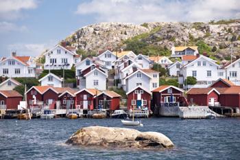 Eine Bucht in Schweden mit kleinen Booten und typisch schwedischen Häuschen im Hintergrund