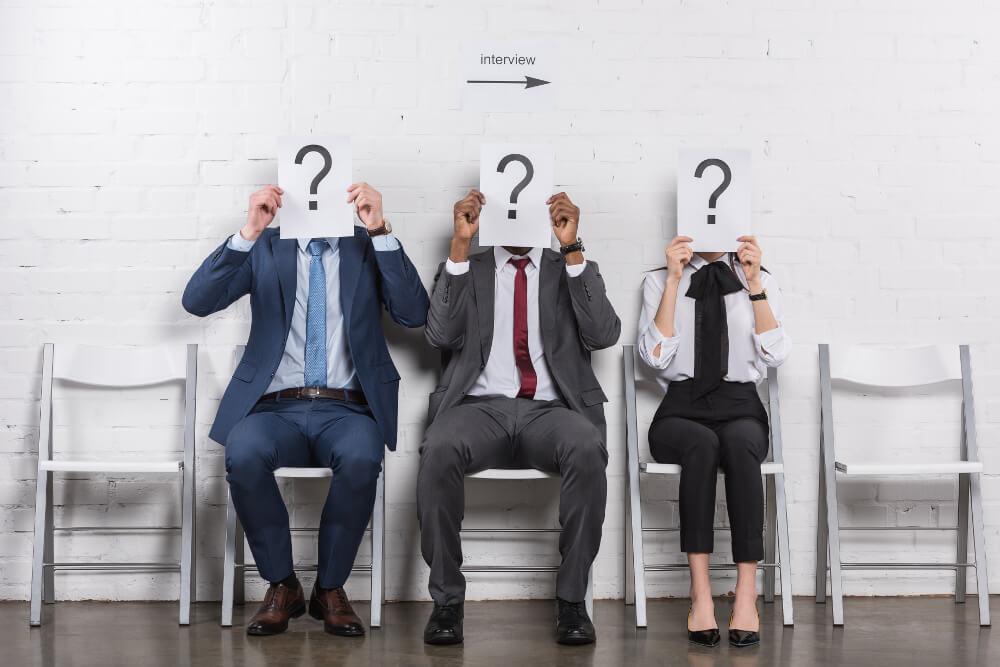 Drei Job-Kandidaten warten gemeinsam auf ihr Vorstellungsgespräch. Um sich unkenntlich zu machen, halten sie jeweils einen Zettel mit einem großen Fragezeichen vor ihr Gesicht.