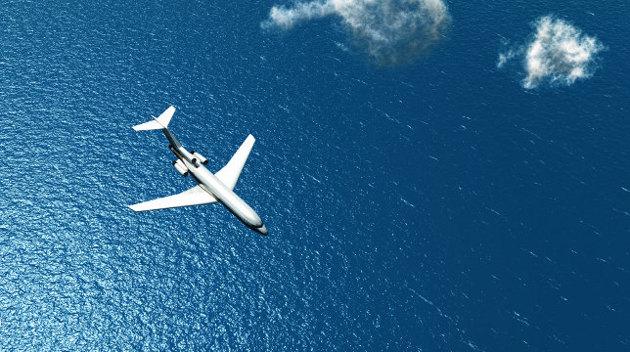 Luftaufnahme eines Flugzeuges, das zwischen wenigen Wolken über einen Ozean fliegt