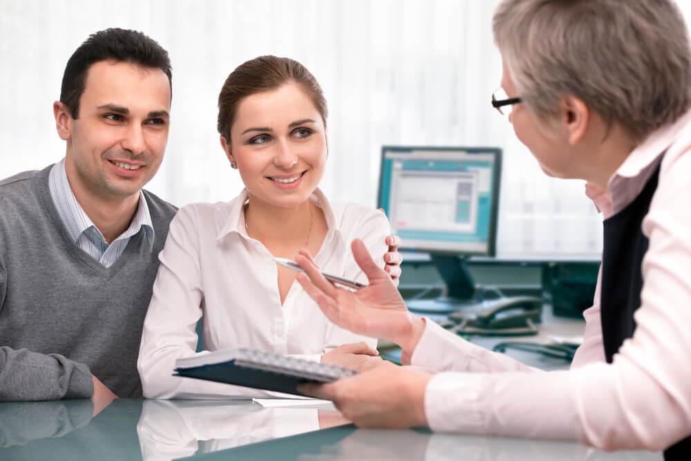 Ein Bankberater informiert ein junges Paar zu Finanzprodukten.