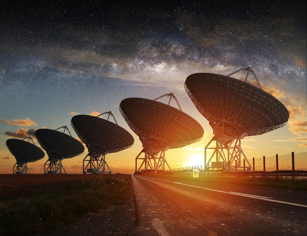 Große Radioteleskope für Astronomen stehen bei untergehender Sonne unter einem Sternenhimmel.