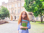 Eine junge Studentin steht vor einem Universitätsgebäude im Ausland.