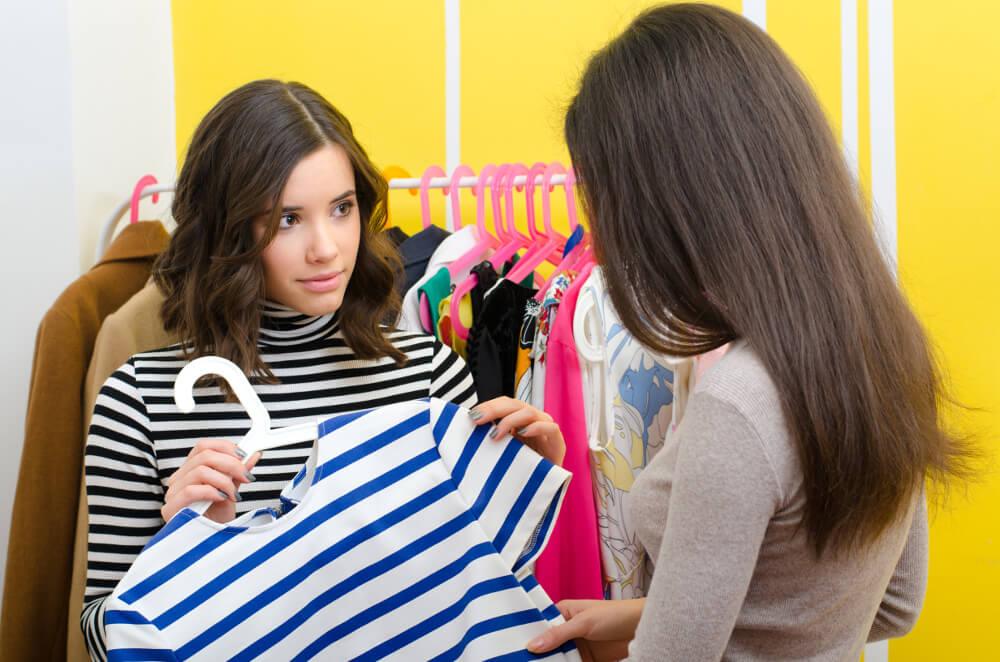 Eine junge Verkäuferin eines Modegeschäfts berät eine Kundin bei der Auswahl eines Kleidungsstückes.