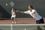 Gemischtes Tennis-Doppel: Der Mann im Vordergrund schnappt der Spielerin im Hintergrund den Ball weg