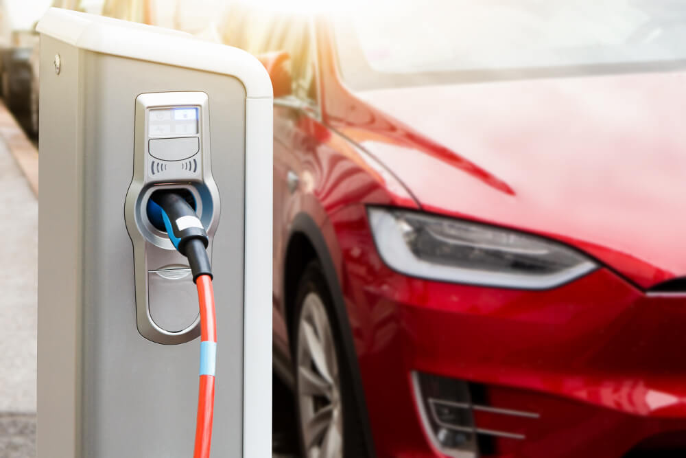 Ein roter Tesla steht vor einer Ladestation.