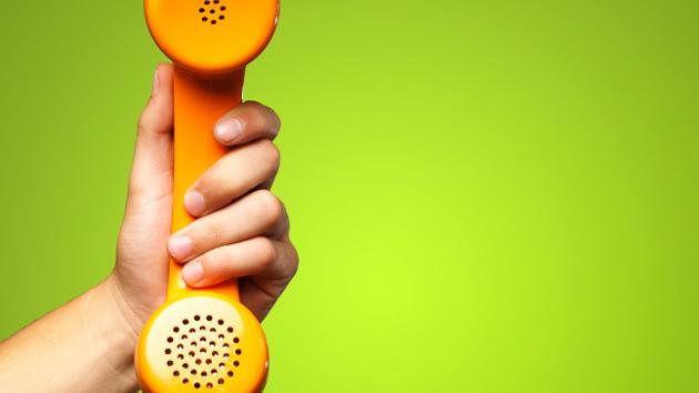Eine Hand hält einen orangenen Telefonhörer vor einem grünen Hintergrund.