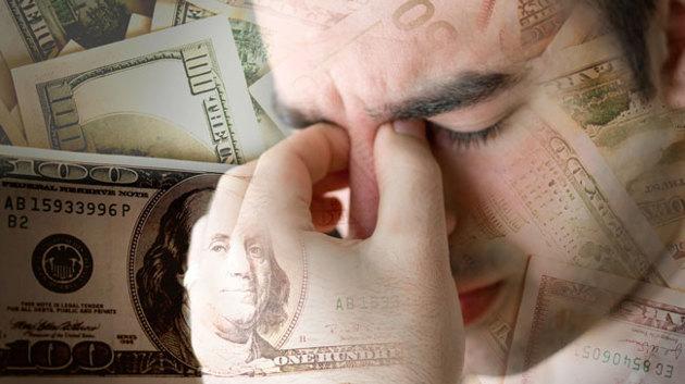 Porträtfoto eines Mannes, der sich vor einem Hintergrund aus Geldscheinen frustriert auf seine Hand stützt.