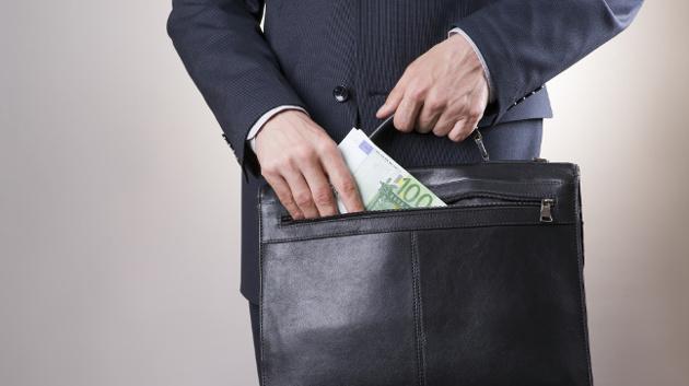 Eine Person in Anzug zieht 100-Euro-Scheine aus ihrer Aktentasche.