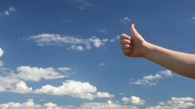 Eine Hand zeigt einen Daumen hoch vorm Himmel.