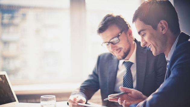 Zwei junge Männer im Anzug arbeiten vor einem Laptop und lächeln.