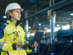 Eine junge Ingenieurin steht mit ihrem Laptop in einer Produktionshalle und analysiert die Vorgänge.