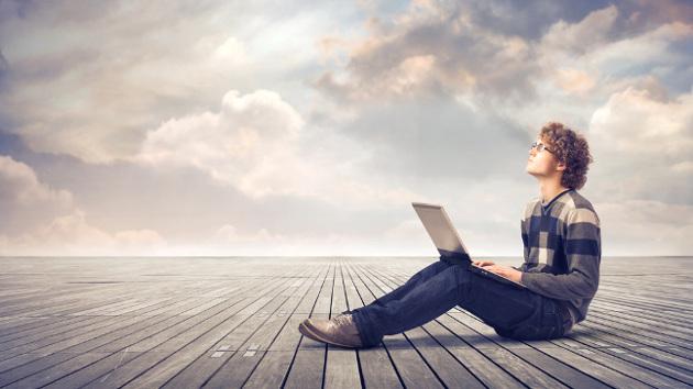 Ein Ausbildungsabsolvent sitzt mit einem Laptop auf einen Holzuntergrund und schaut in Richtung Himmel.
