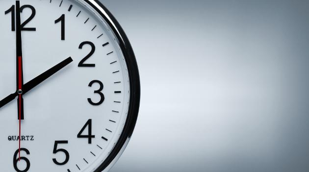 Eine zur Hälfte zu sehende runde Uhr vor einem grauen Hintergrund zeigt die Tageszeit 14 Uhr an.