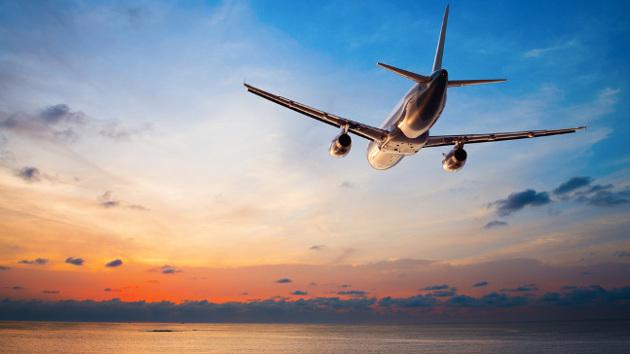 Ein Flugzeug fliegt über den Ozean in Richtung Sonne.