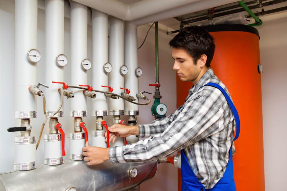 Ein junger Heizungstechniker arbeitet an einer Heizungsanlage.