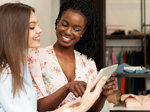 Eine Verkäuferin im Modegeschäft zeigt einer jungen Kundin Produkte auf einem Tablet.