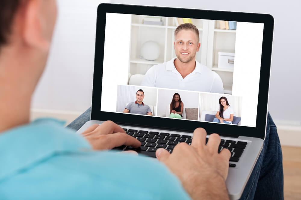 Ein junger Mann nimmt vom Homeoffice aus an einer Videokonferenz mit Kolleginnen und Kollegen teil.