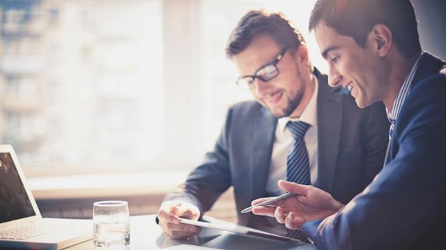 Zwei Geschäftsmänner sitzen am Schreibtisch vor einem Laptop und schauen auf ein Tablet.