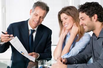 Ein Bankberater berät ein junges Pärchen zu Finanzprodukten.