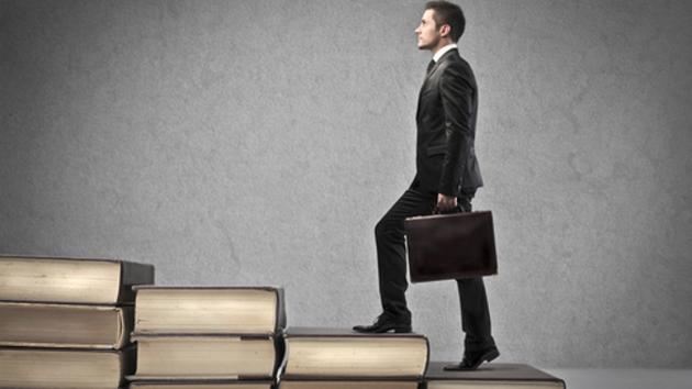 Ein Mann in Anzug und mit Aktentasche in der Hand steigt eine aus Büchern bestehende Treppe nach oben.