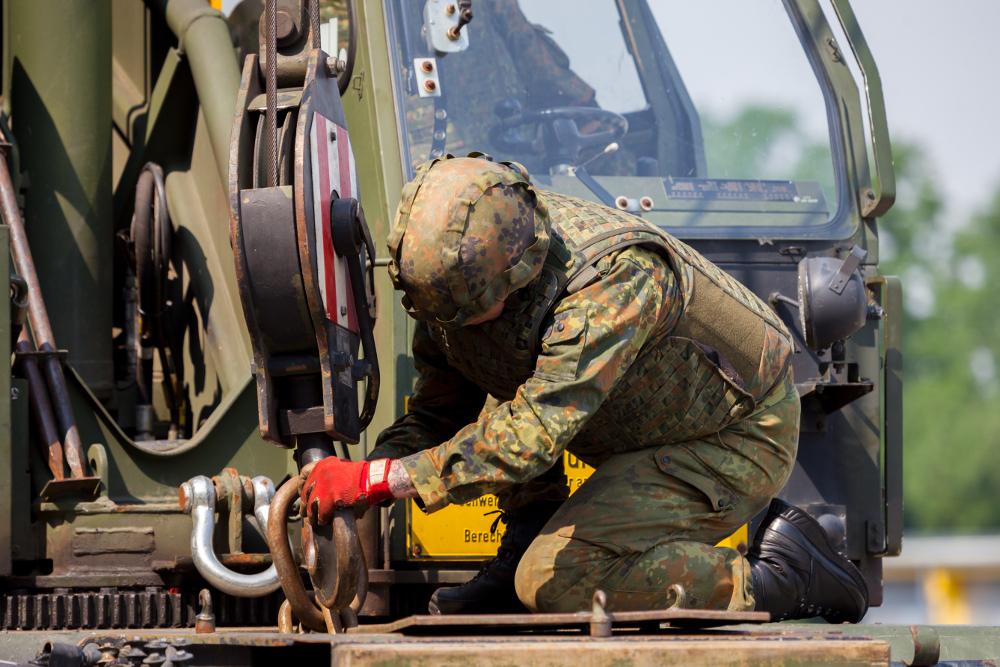 Ein Soldat der Bundeswehr repariert schweres technisches Gerät