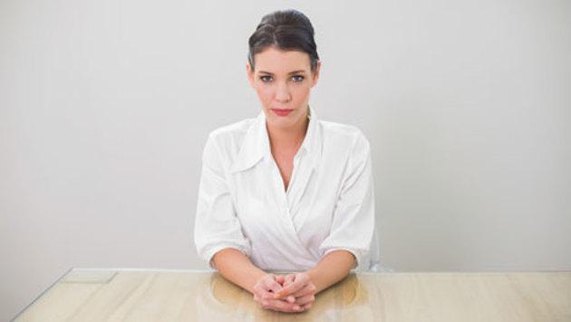 Eine Frau in weißem Hemd sitzt mit enttäuschtem Gesichtsausdruck an einem Schreibtisch.