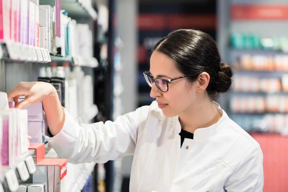 Eine junge Drogistin kümmert sich am Regal eines Drogeriemarktes um die Warenpräsentation.