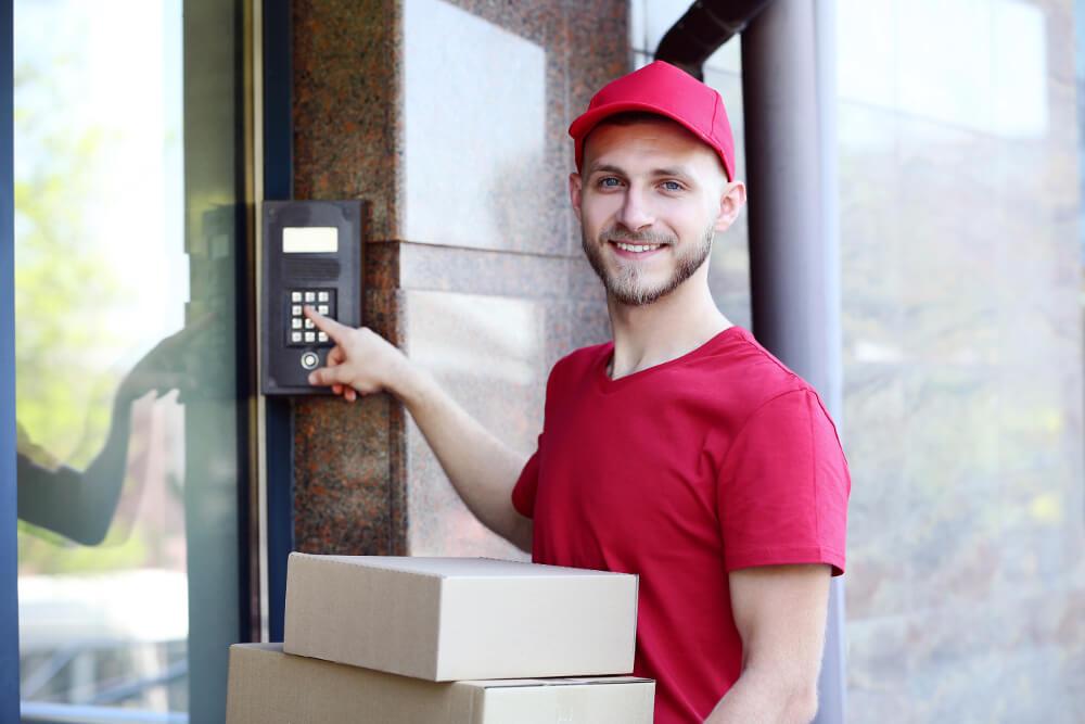 Ein junger Paketbote im roten Dress (DPD) klingelt an einer Haustür.