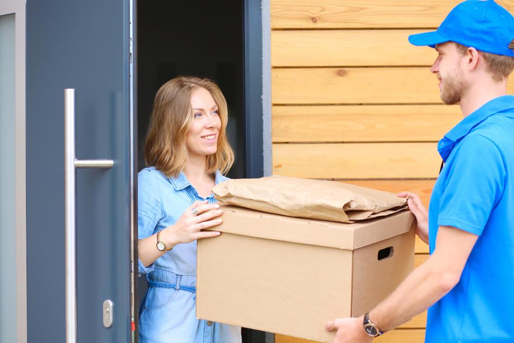 Ein Hermes-Paketbote übergibt einer Empfängerin ein Paket an der Haustür.