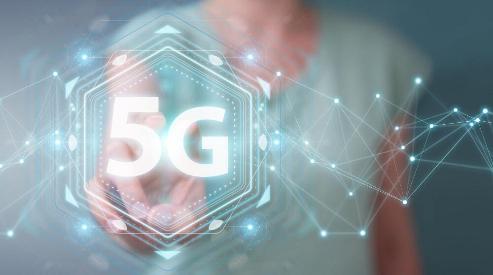 Eine Projektion zu 5G wird an einem interaktiven Board von einer Frau bearbeitet.