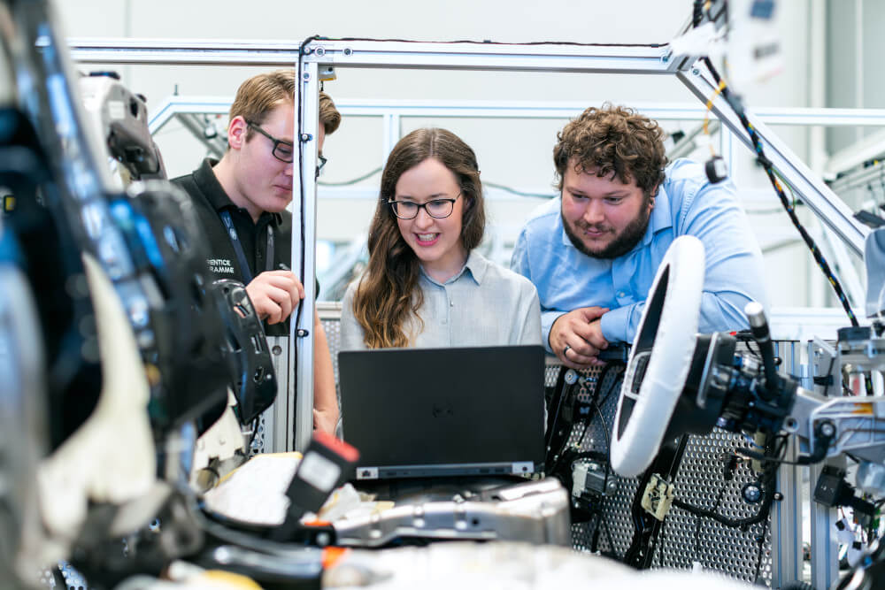 Ingenieure In einer Autowerkstatt schauen sich an einem Computer die neusten Entwicklungen an