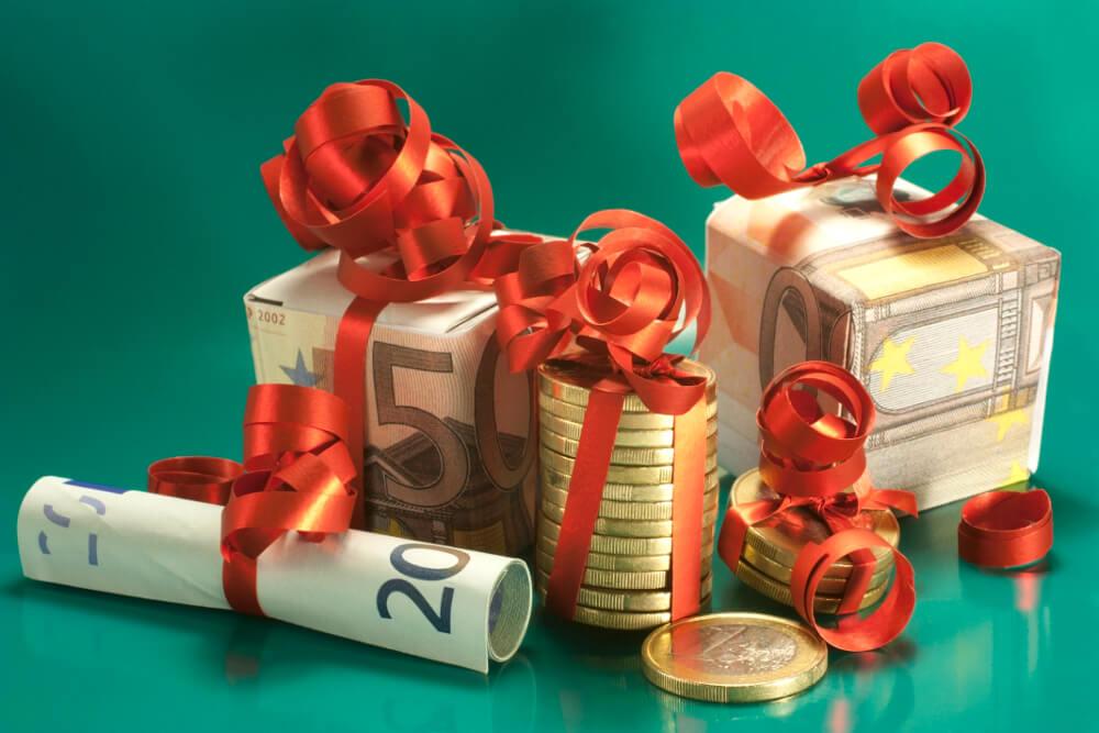 Münzen und Geldscheine verpackt wie kleine Geschenke.