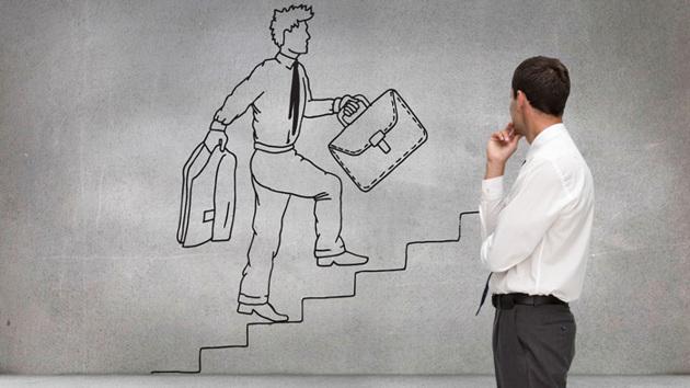 Ein Mann in Anzug steht vor einer Wandzeichnung eines Geschäftsmannes, der eine Treppe hochsteigt.