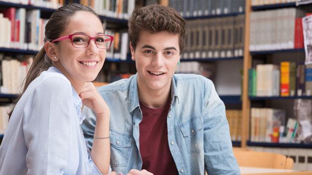 Zwei Studierende sitzen in der Bibliothek und lächeln.