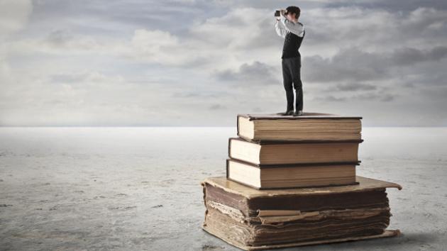 Eine kleine Person steht auf einem Stapel alter Bücher und schaut durch ein Fernglas in die Ferne.